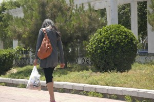 A Lady Walks Home After Using a Credit Card to Pay for Groceries