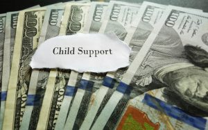 Closeup of hundred dollar bills with Child Support note
