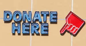 "Sign that reads ""donate here"" encourages charitable giving."