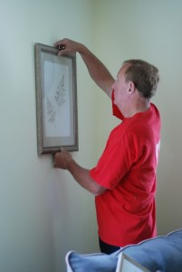man decorating a first home by hanging pictures
