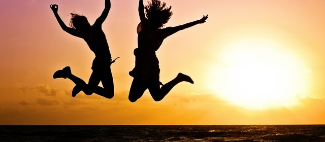 Two people jumping at a sunset